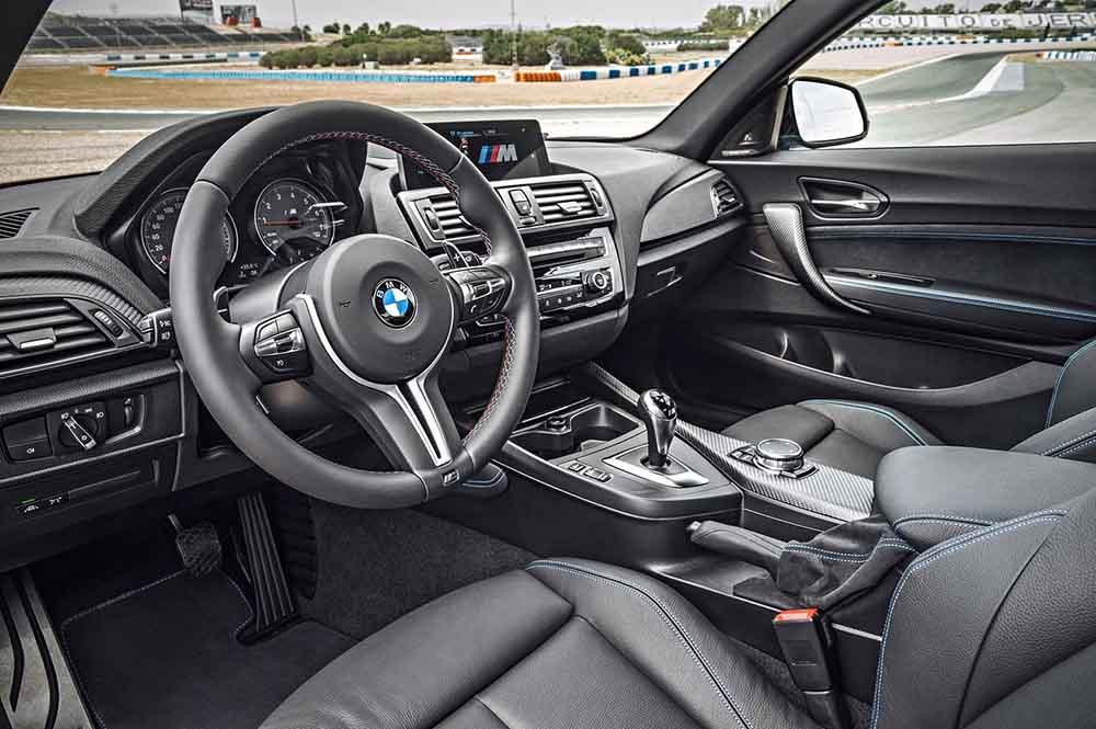 Интерьер BMW M2 в тёмных тонах с синей строчкой