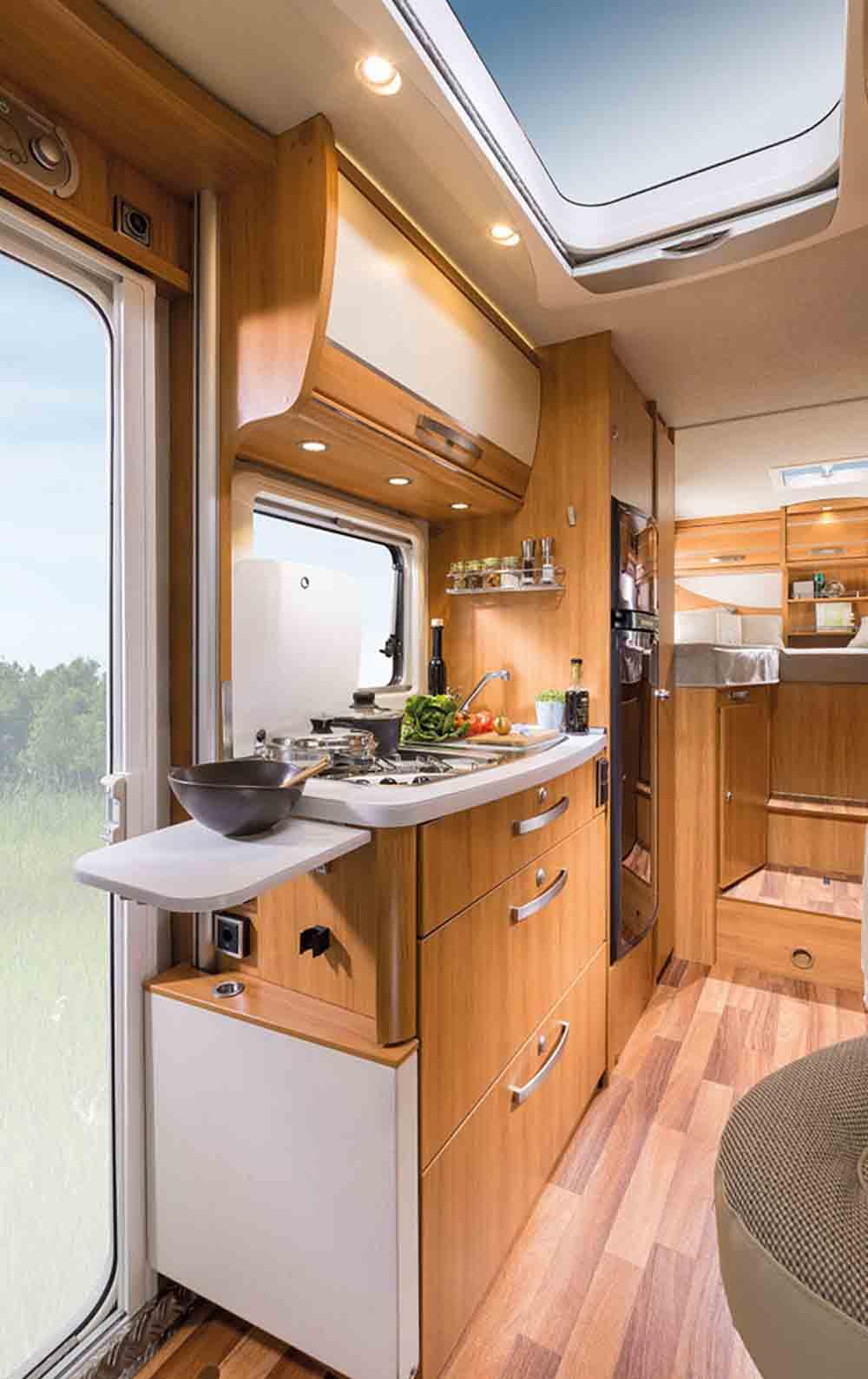 Кухня автодома с плитой, холодильником и проточной водой