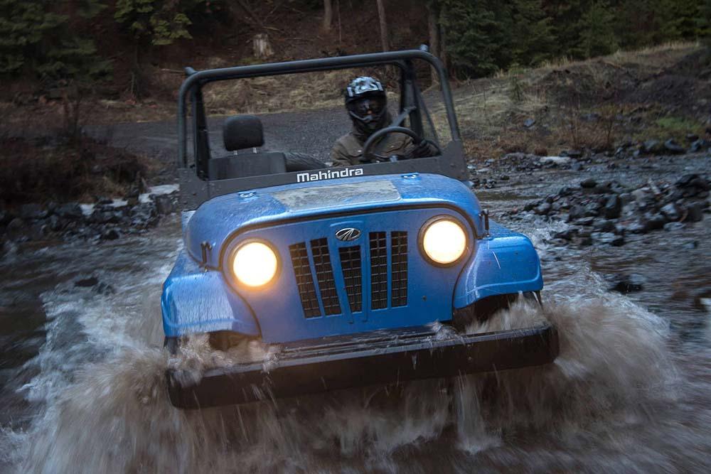 Машина с синим кузовом преодолевает реку вброд